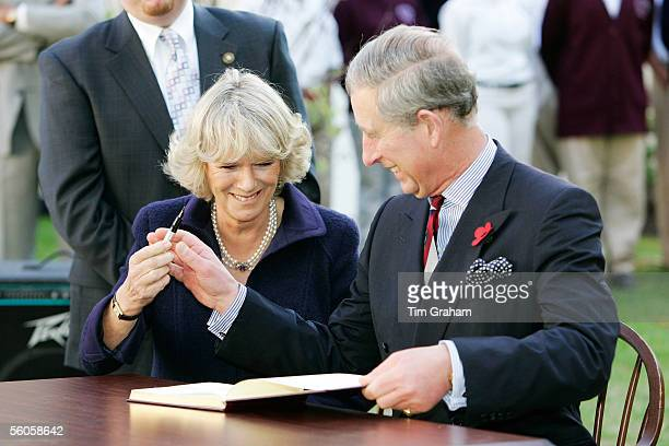 Prince Charles Prince of Wales and Camilla Duchess of Cornwall giggle as she is reluctant to return his pen as they sign the visitors' book at SEED...