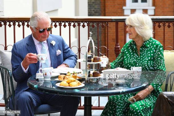 Prince Charles, Prince of Wales and Camilla, Duchess of Cornwall have tea on the terrace during a visit to Theatre Royal on June 23, 2021 in London,...