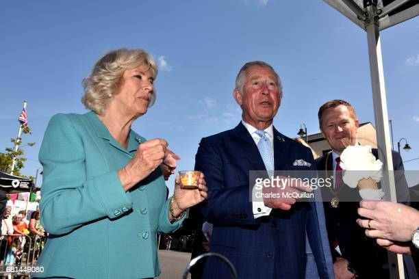 Prince Charles Prince of Wales and Camilla Duchess of Cornwall laugh as they share an ice cream on their visit to the village market on May 10 2017...