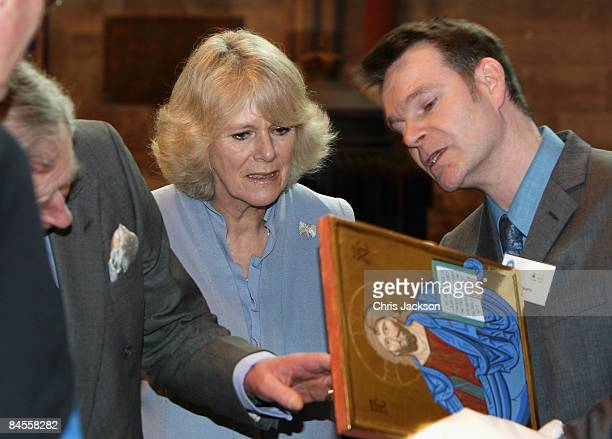 Prince Charles Prince of Wales and Camilla Duchess of Cornwall look at a religious icon they were given as a gift as they tour Hereford Cathederal on...