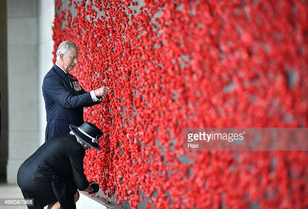 Prince Charles Prince of Wales and Camilla Duchess of Cornwall place poppies on the Roll of Honour at the Australian War Memorial on November 11 2015...