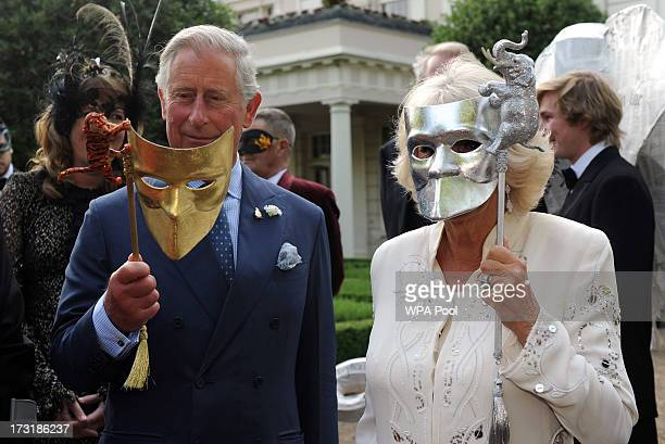Prince Charles Prince of Wales and Camilla Duchess of Cornwall pose with masks as they host a reception for the Elephant Family a charity working to...