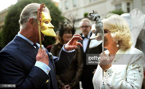 Prince Charles, Prince of Wales and Camilla, Duchess of Cornwall pose with masks as they host a reception for the Elephant Family, a charity working...