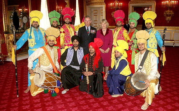Prince Charles Prince of Wales and Camilla Duchess of Cornwall pose with traditional Sikh bhangra dancers at the Sikh religious and cultural festival.