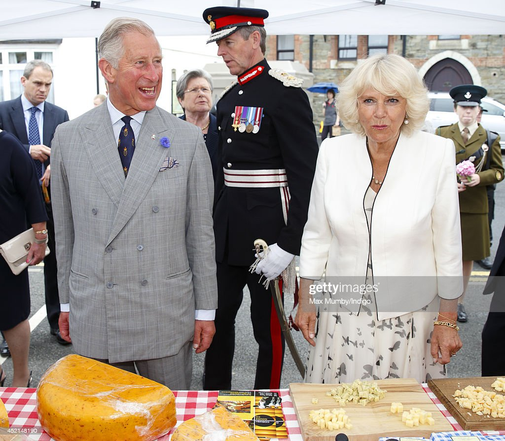Prince Charles, Prince of Wales and Camilla, Duchess of Cornwall sample some cheese as they tour a market on day one of their annual visit to Devon and Cornwall on July 14, 2014 in Looe, England.