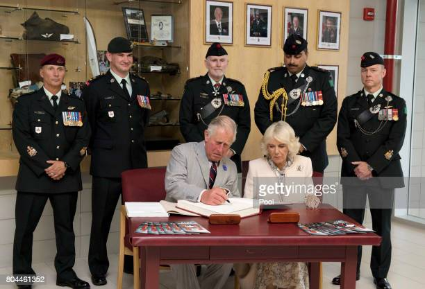 Prince Charles Prince of Wales and Camilla Duchess of Cornwall sign a guest book during a visit to the Canadian Forces Base Trenton during a 3 day...