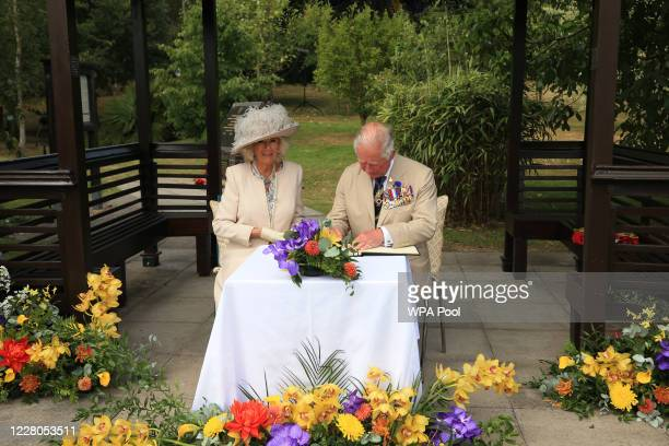 Prince Charles Prince of Wales and Camilla Duchess of Cornwall sign the visitors book during the national service of remembrance marking the 75th...