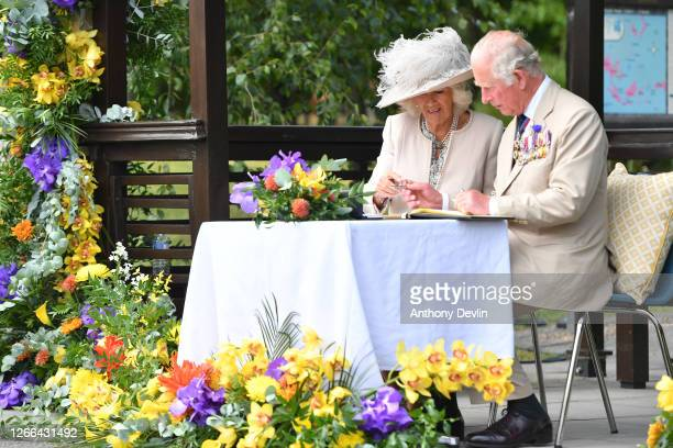 Prince Charles Prince of Wales and Camilla Duchess of Cornwall sign the guest book as they attend a national service of remembrance marking the 75th...