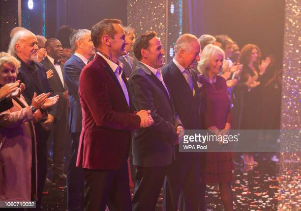 Prince Charles Prince of Wales and Camilla Duchess of Cornwall stand on stage with comedians Alexander Armstrong and Ben Miller after attending a one...