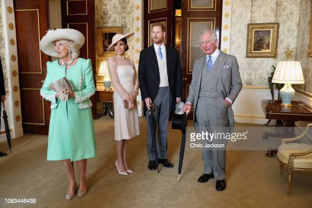 Prince Charles, Prince of Wales and Camilla, Duchess of Cornwall stand with Meghan, Duchess of Sussex and Prince Harry, Duke of Sussex as they look...