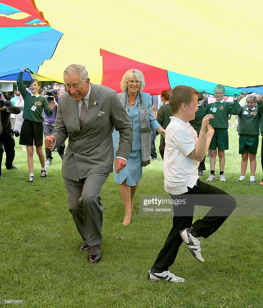 Prince Charles, Prince of Wales and Camilla, Duchess of Cornwall take part in a Youth Showcase 'Parachute game' during a visit to Saumarez Park on July 19, 2012 in St Peter's Port, United Kingdom. The Prince of Wales and the Duchess of Cornwall are in Guernsay as part of a Diamond Jubilee visit to the Channel Islands taking in Jersey, Guernsey and Sark