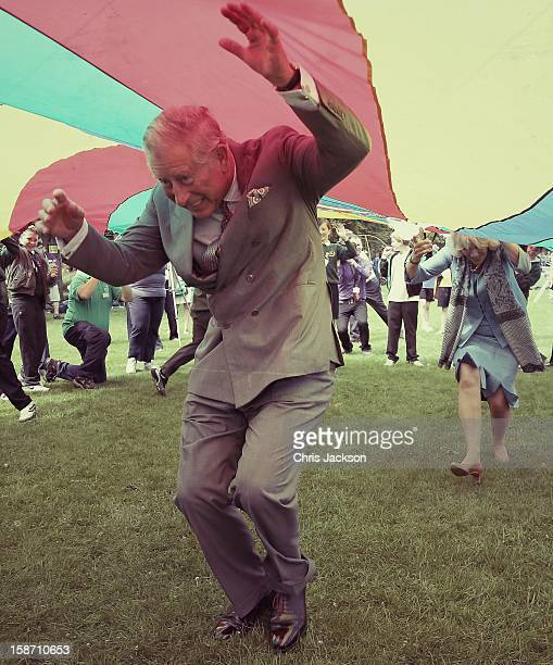 Prince Charles, Prince of Wales and Camilla, Duchess of Cornwall take part in a Youth Showcase 'Parachute game' during a visit to Saumarez Park on...