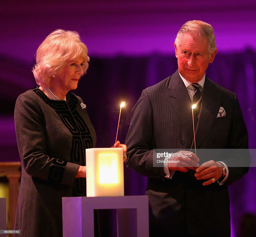 Prince Charles, Prince of Wales and Camilla, Duchess of Cornwall take part in a candle lighting ceremony on stage as they attend a Holocaust Memorial Day Ceremony at Central Hall Westminster on January 27, 2015 in London, England.
