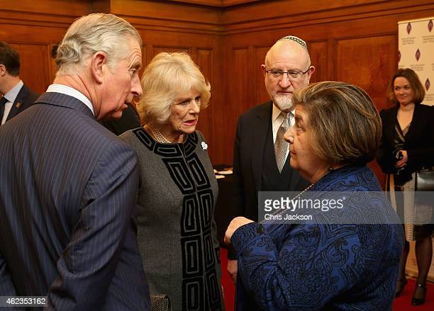 Prince Charles Prince of Wales and Camilla Duchess of Cornwall talk to Holocaust survivor Agnes GrunwaldSpier as they attend a Holocaust Memorial Day...