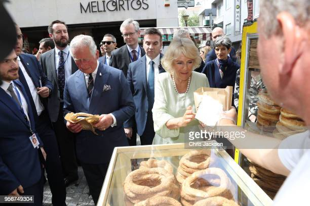 Prince Charles Prince of Wales and Camilla Duchess of Cornwall talk to a street vendor serving and try koulouri a traditional Greek pretzel during a...