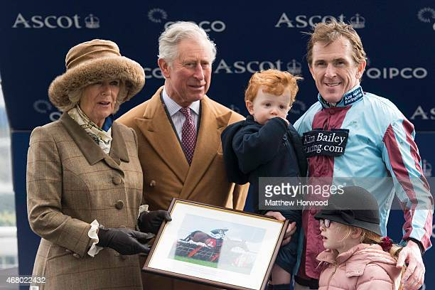 Prince Charles Prince of Wales and Camilla Duchess of Cornwall present Tony McCoy and his children Evie and Archie Peader with a framed print on his...
