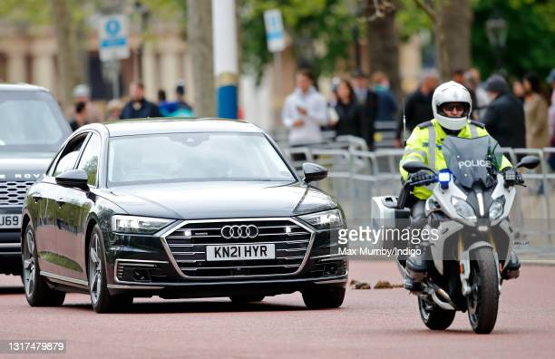 Prince Charles, Prince of Wales and Camilla, Duchess of Cornwall travel down The Mall, in their chauffeur driven Audi A8 car led by a motorcycle...