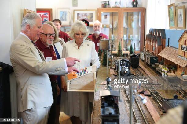Prince Charles Prince of Wales and Camilla Duchess of Cornwall try out a model railway as they help mark the 150th anniversary of the Heart of Wales...