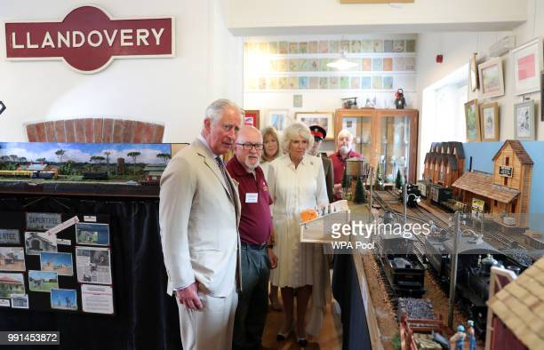 Prince Charles Prince of Wales and Camilla Duchess of Cornwall try out a model as they mark the 150th anniversary of the Heart of Wales railway line...
