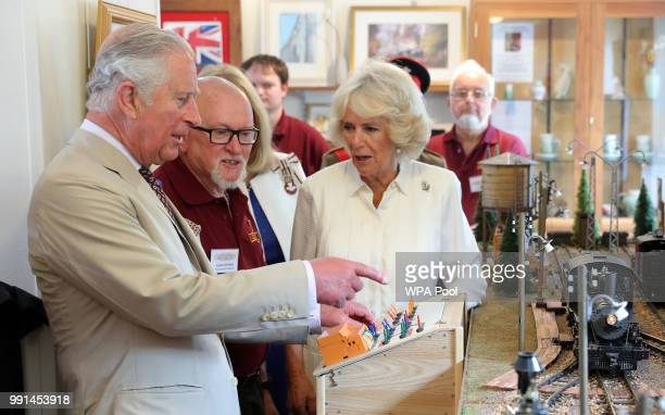 Prince Charles Prince of Wales and Camilla Duchess of Cornwall try out a model railway as they mark the 150th anniversary of the Heart of Wales...