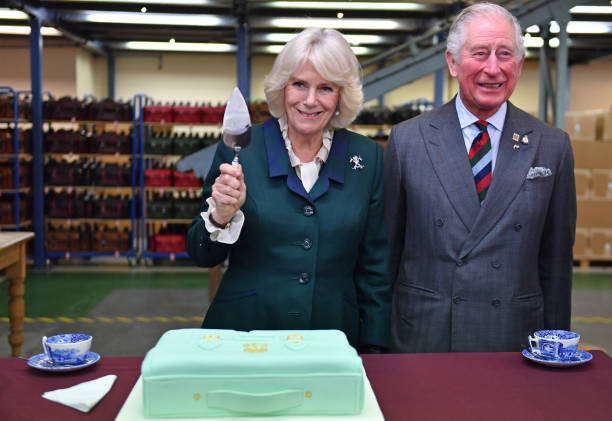 Prince Charles Prince of Wales and Camilla Duchess of Cornwall with a presentation cake during a visit to The Cambridge Satchel Company where they...