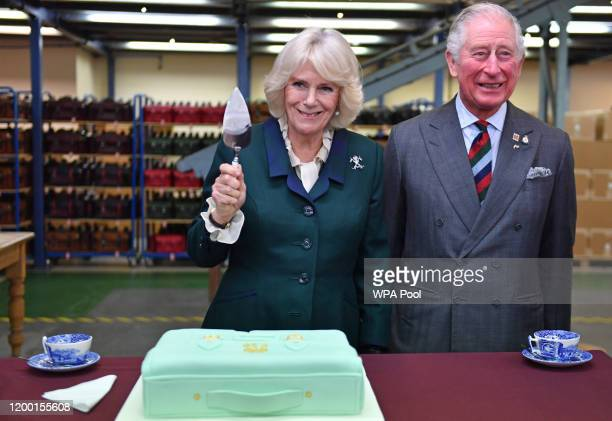 Prince Charles, Prince of Wales and Camilla, Duchess of Cornwall with a presentation cake during a visit to The Cambridge Satchel Company, where they...
