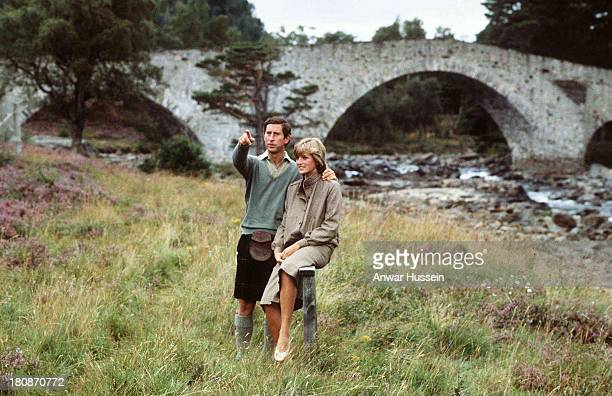 Prince Charles, Prince of Wales and Diana, Princess of Wales, wearing a suit designed by Bill Pashley, pose for a photo on the banks of the river Dee...