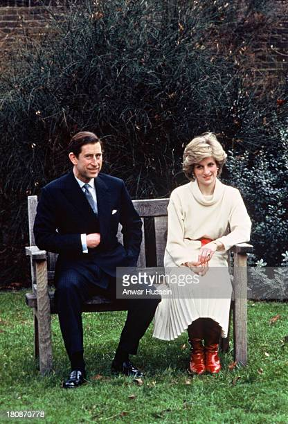 Prince Charles, Prince of Wales and Diana, Princess of Wales, wearing a cream cowl neck jumper and pleated skirt with a red belt and boots, sit on a...