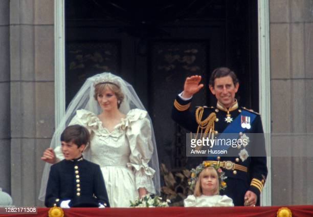 Prince Charles, Prince of Wales and Diana, Princess of Wales, whose wedding dress was designed by David and Elizabeth Emanuel, wave from the balcony...