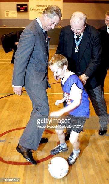 Prince Charles Prince of Wales and former England football captain Jimmy Armfield attempt to tackle nineyearold Callum Atkinson during a coaching...