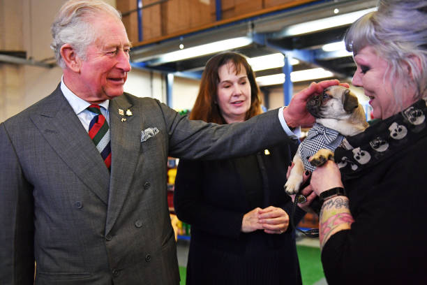 Prince Charles Prince of Wales and founder Julie Deane meet an employee and her dog during a visit to The Cambridge Satchel Company where he toured...