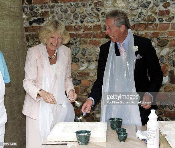 Prince Charles Prince of Wales and his wife Camilla Duchess of Cornwall wearing aprons laugh as they try modelling ceiling tiles during a visit to...