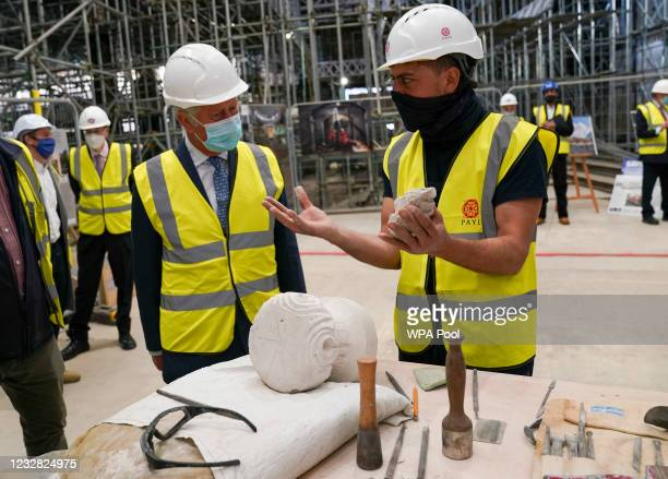 Prince Charles, Prince of Wales chats to stonemason Louis Clark as he views construction and preservation work being undertaken in preparation for...