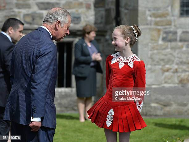 Prince Charles Prince of Wales chats with a young Irish dancr as they visit Donegal Castle on May 25 2016 in Letterkenny Ireland The royal couple are...