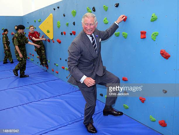 Prince Charles Prince of Wales climbs on the new traversing wall in the new gym at Grainville Secondary School on July 18 2012 in St Helier United...