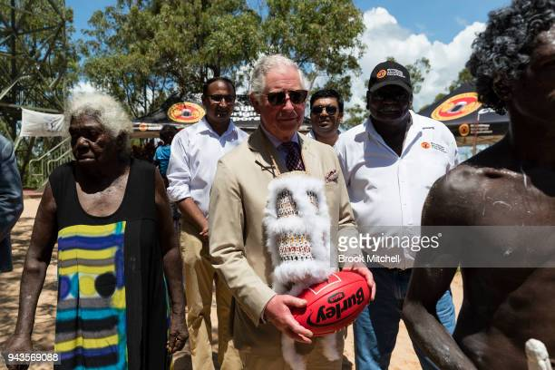 Prince Charles Prince of Wales clutches an Australian Rules Football gifted to him after a Welcome to Country Ceremony on April 9 2018 in Gove...