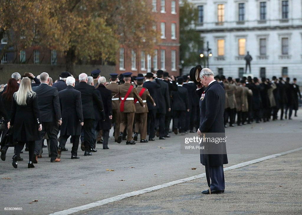Prince Charles, Prince of Wales doffs his hat to members of the Welsh Guard parading past, after he laid a wreath at the Guard's Memorial for the Welsh Guards' Regimental Remembrance Sunday on November 13, 2016 in London, England. The Queen, senior politicians, including the British Prime Minister and representatives from the armed forces pay tribute to those who have suffered or died at war.