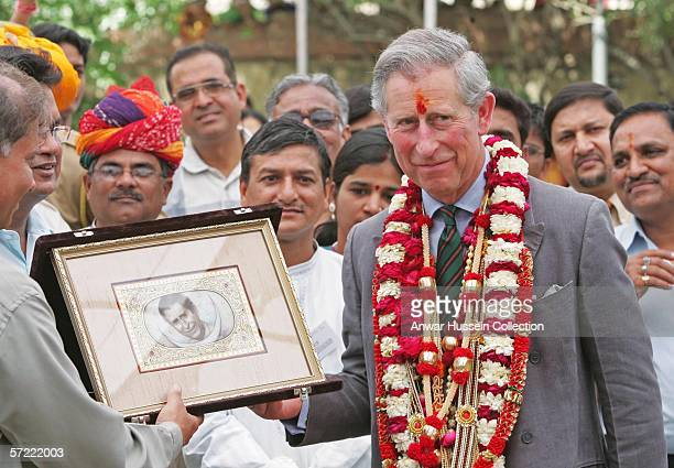 Prince Charles Prince of Wales garlanded and with a tilak mark on his forehead receives a picture of himself as he takes a walking tour of the Old...