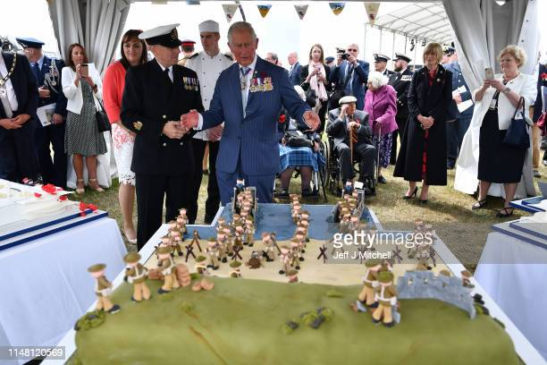 Prince Charles Prince of Wales gestures as he looks at a DDay themed cake during the Dday 75 Commemorations on June 05 2019 in Portsmouth England The...