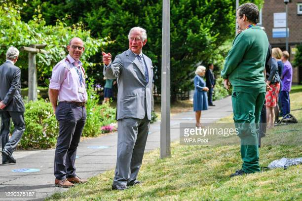 Prince Charles, Prince of Wales gestures to crowds of hospital staff watching from a distance as he chats with front line key workers who who have...
