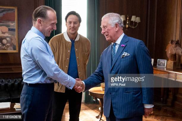 Prince Charles , Prince of Wales greets British actor Ralph Fiennes and US Director Cary Joji Fukunaga as he tours the set of the 25th James Bond...