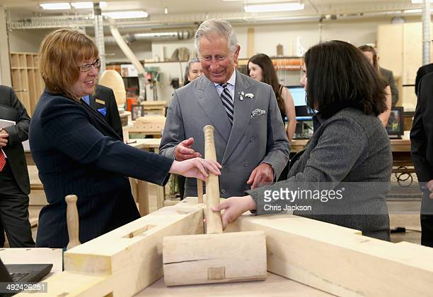 Prince Charles Prince of Wales hammers in a peg with a giant mallet as he visits the woodwork department at the centre for applied science and...