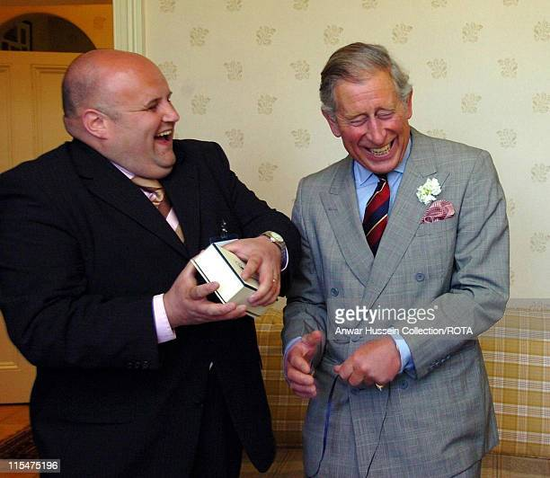 Prince Charles Prince of Wales has difficulty opening a present as he visits Neuadd Lwyd a country house bed and breakfast establishment in Penmynydd...