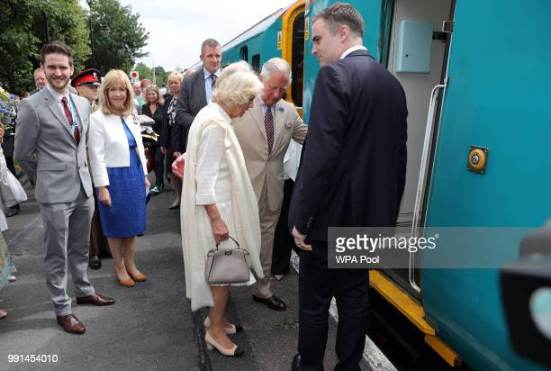 Prince Charles Prince of Wales helps Camilla Duchess of Cornwall board a train after they mark the 150th anniversary of the Heart of Wales railway...