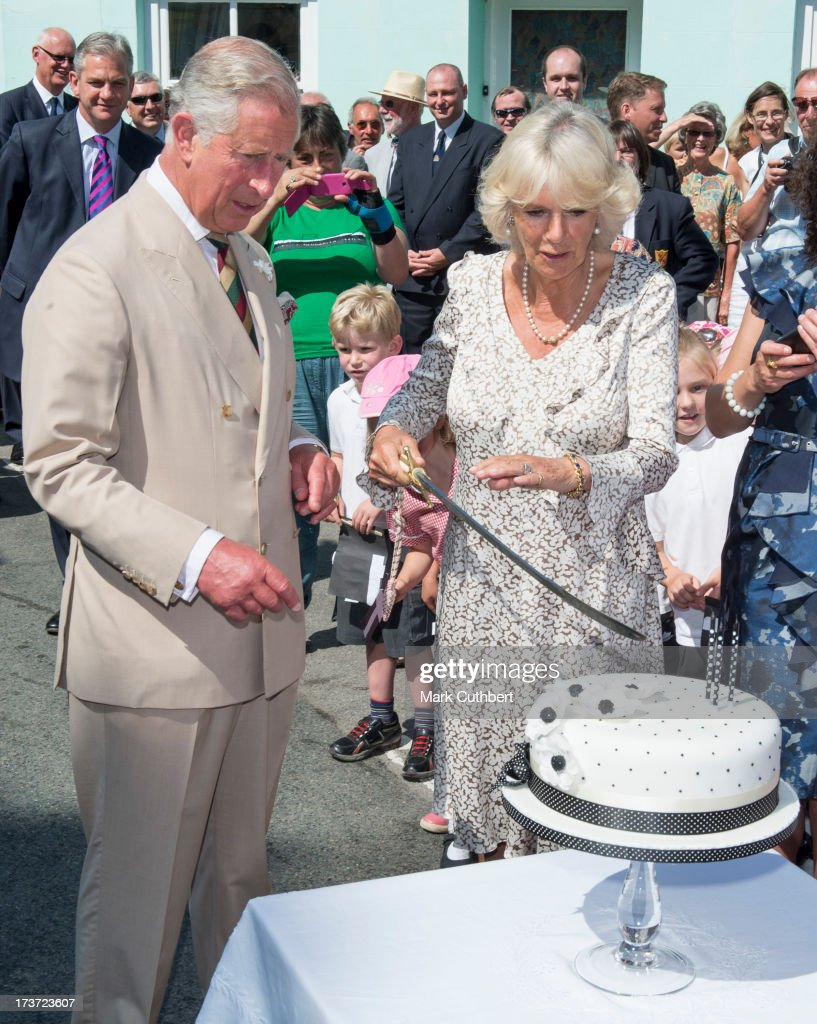 Prince Charles, Prince of Wales helps Camilla, Duchess of Cornwall, to cut a birthday cake on her 66th birthday, during a walkabout on a visit to Lostwithiel on July 17, 2013 in Cornwall, England.