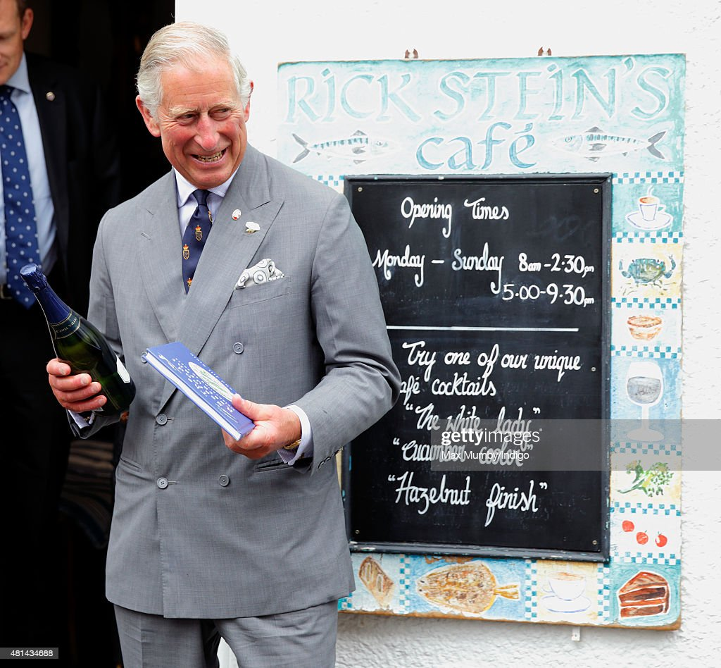 Prince Charles, Prince of Wales holds a bottle of Camel Valley sparkling wine and a book commemorating the 40th anniversary of Rick Stein's Seafood Restaurant during a visit to Rick Stein's Cafe as he and Camilla, Duchess of Cornwall visit Padstow on day 1 of their annual summer tour of Cornwall on July 20, 2015 in Padstow, England.