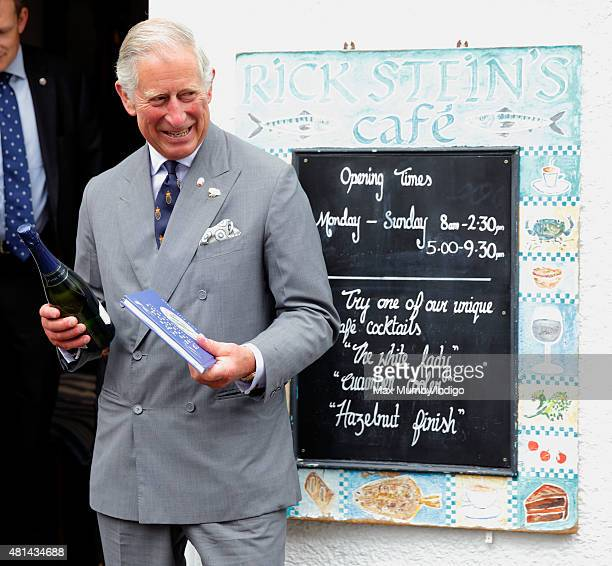Prince Charles Prince of Wales holds a bottle of Camel Valley sparkling wine and a book commemorating the 40th anniversary of Rick Stein's Seafood...