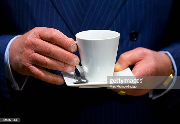 Prince Charles Prince of Wales holds a cup and saucer as he accompanied by Jamie Oliver visits Carshalton Boys Sports College to see how the school...