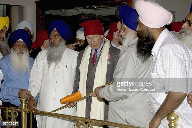 Prince Charles Prince of Wales holds a Sikh sword when he visits the Anadpur Sahib Gurdwara on the eighth day of a 12 day official tour visiting...