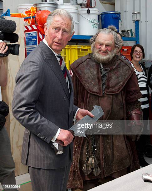 Prince Charles, Prince of Wales holds a sword after meeting Mark Hadlow who plays Dori in the new 'Hobbit' film at Weta Workshop on November 14, 2012...